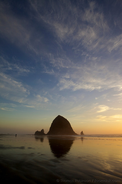 Cirrostratus clouds hang high above Haystack Rock just before sunset in Cannon Beach, Oregon.
