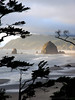Haystack Rock in Cannon Beach, Oregon, glows in the evening light from the Silver Point viewpoint. Photos of Cannon Beach, one of the most picturesque Oregon beaches.