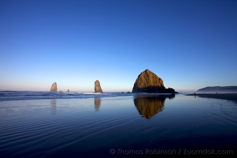 The reflective sand mirrors Haystack Rock at sunrise.