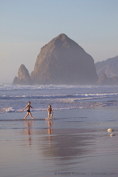 Two children play on along the Cannon Beach shoreline.