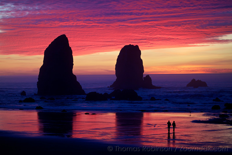 A couple strolls on the wet reflective sand near Haystack Rock and the Needles during a vibrant sunset in Cannon Beach, Oregon.