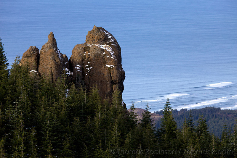 Snow dusts a rock outcropping above the Pacific Ocean near Angora Peak along the Oregon Coast.