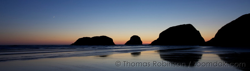 Cannon Beach Evening Panorama - The Crescent Moon sparkles in the twilight glow above Bird Rocks in Cannon Beach, Oregon.