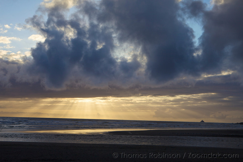 God beams (crepuscular rays) break through the clouds over Ecola Creek in Cannon Beach, Oregon.