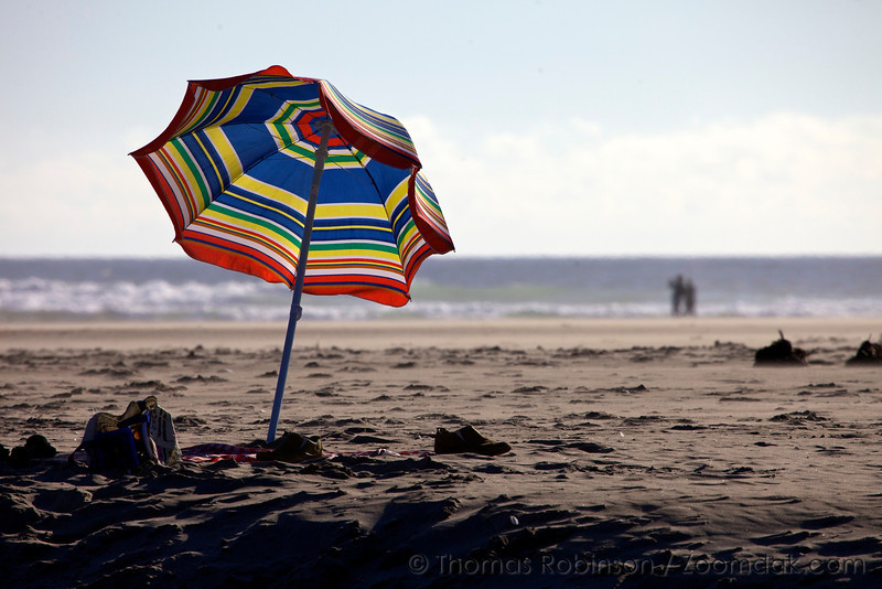 A colorful umbrella perched in the sand on a perfect day in Cannon Beach, Oregon.