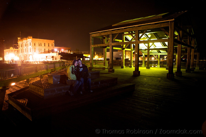 Jonathan and Christina Robinson sit on a dock together in Port Townsend, looking out into the starry bay.