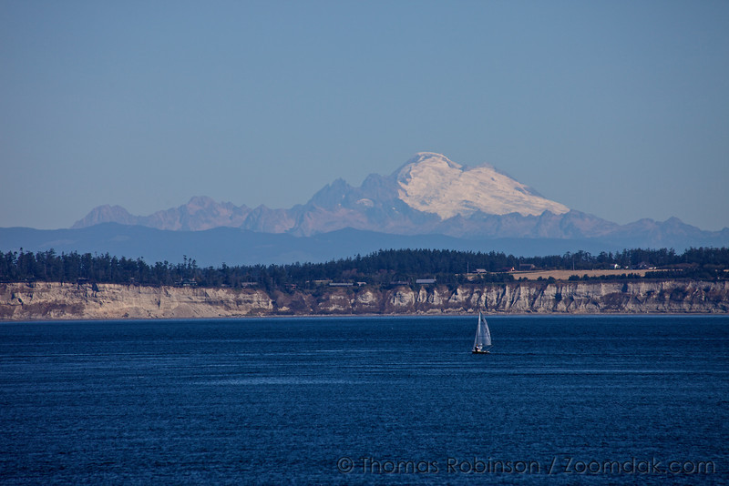 A sailboat floats on the Puget Sound in front of Mt. Baker.