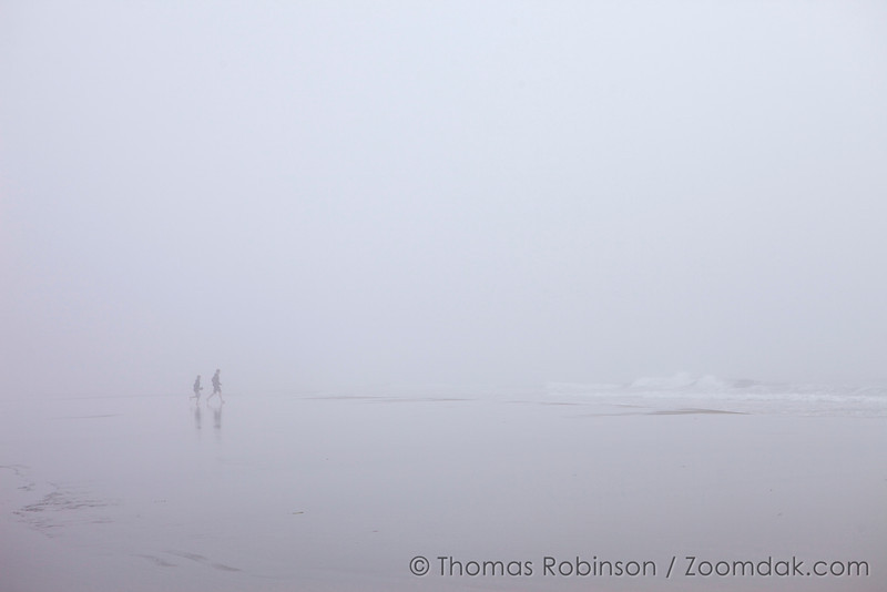 Two tourists run towards the ocean on a foggy day in Cannon Beach, Oregon. The Fog Runners