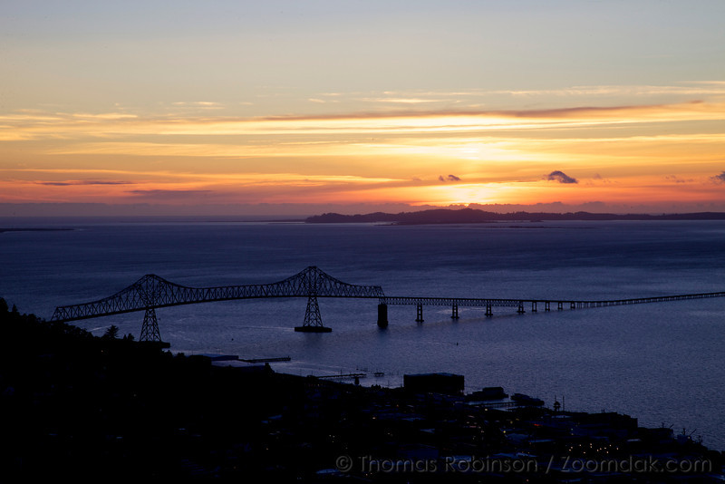 The Astoria-Megler Bridge stands silhouetted above the Columbia River in Astoria Oregon. Constructed of steel with 171 piers in the water, its total length is 21,474 feet (6,545 m).