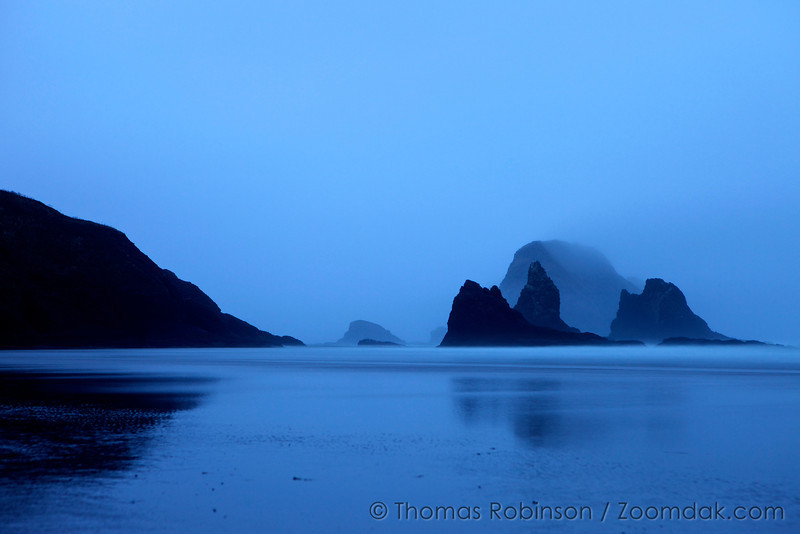 The windblown seastacks of the three capes near Oceanside stand tall on a misty blue evening.