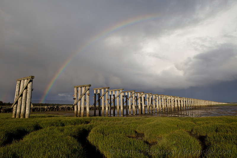 A rainbow shines above the old train trestle across Trestle Bay near the Columbia River in Fort Stevens State Park.