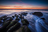 Waves charge through this unusual beach rock formation at sunset in Arcadia State Park on the Oregon Coast.
