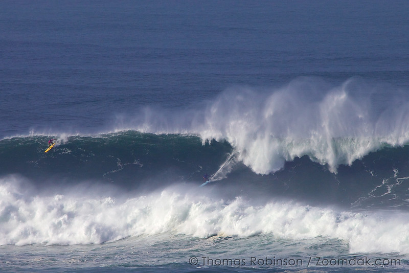 Two surfers ride a huge 30-40ft wave at the Nelscott Reef Contest 2010.