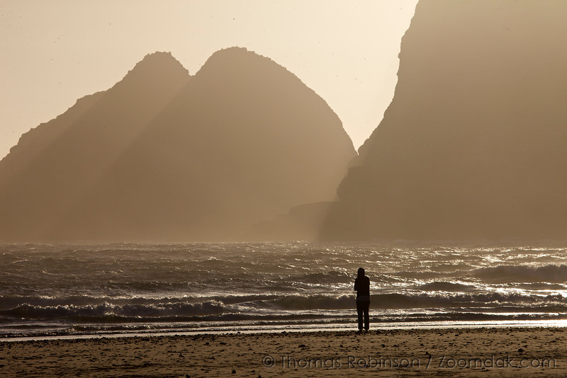 A woman stands silhouetted, contemplating the ocean as God beams (crepuscular rays) shine through the mist of Three Arch Rocks in Oceanside, Oregon.