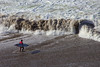 A surfer walks toward a giant 8-10ft wall of white water at Nelscott Reef Surf Contest 2010.