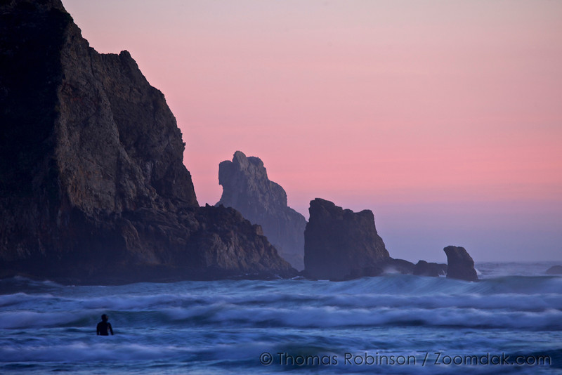 A surfer looks out at the last waves of the day at Shortsands Beach (also called Smuggler's Cove) in Oswald West State Park.