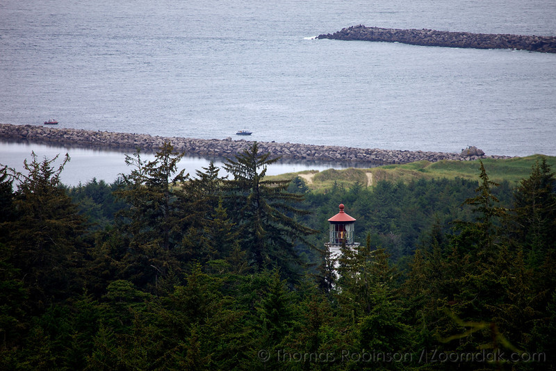 The Umpqua Lighthouse, also known as the Umpqua River Light, through the trees above the Umpqua River on the Oregon Coast.