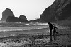 A girl frolics while following her father along the rocky shoreline of Oceanside, Oregon.