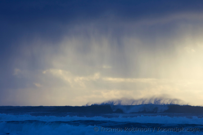 Rain falls from the clouds onto the crash waves below.