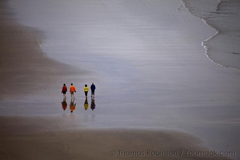 A family of 4, al in different colors, stroll the beach. Oregon Coast beaches provide wide expanse of walking and hiking.