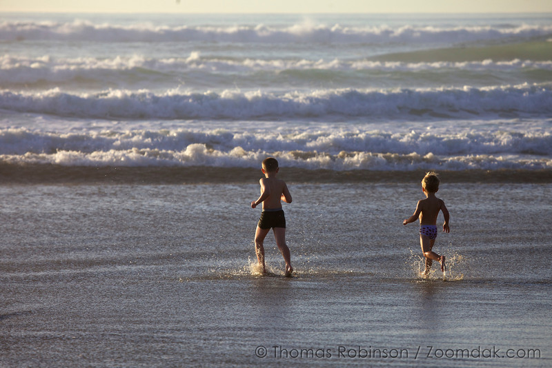 Two children chase the waves, a day full of play.