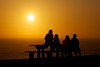 A family watches the sun go down over the Pacific Ocean.