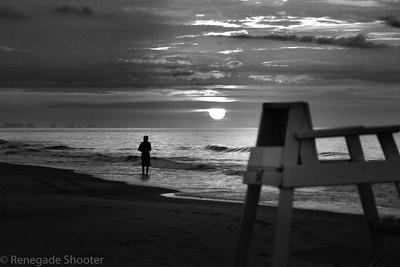 b-w guy fishing from beach sunset