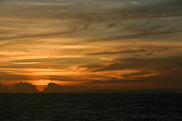 Sunset over the island of Ni'ihau, as viewed from a boat just offshore from the Na Pali coast, west Kaua'i. The island is visible on the horizon just to the right of the setting sun.