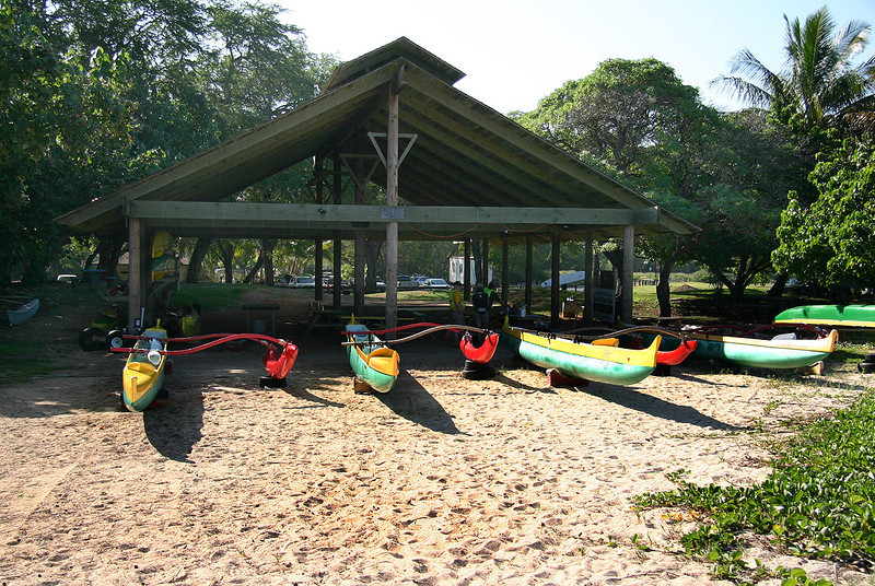 Racing canoes fitted with their outriggers, prepped and ready for the day's paddling. Canoe Hale at Kanaha Beach, Kahului, north Maui.