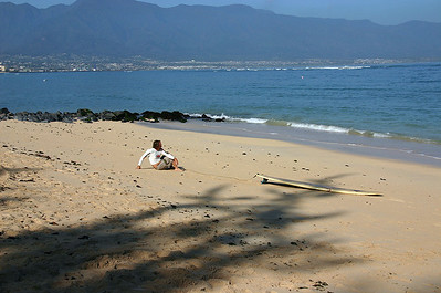 A morning surfer contemplates the wavesets at Kanaha Beach, Kahului, Maui.