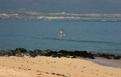 A traditionalist paddling his board in the early morning surf at Kanaha Beach, Kahului, North Maui.