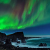 Stars and Aurora Borealis streaming over sea stacks, waves and rocky shoreline of the Greenland Sea on the Reykjanes Peninsula, Iceland