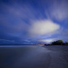 Stars and meteors breaking through the clouds above Turner Beach in the Gulf of Mexico on Captiva Island, Florida