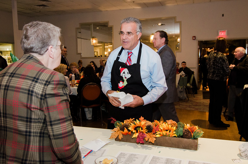Mayor Dean Mazzarella acts as a celebrity waiter during the annual Beacon of Hope Harvest Dinner Dance at the Leominster Elks Lodge on Friday evening. SENTINEL & ENTERPRISE / Ashley Green