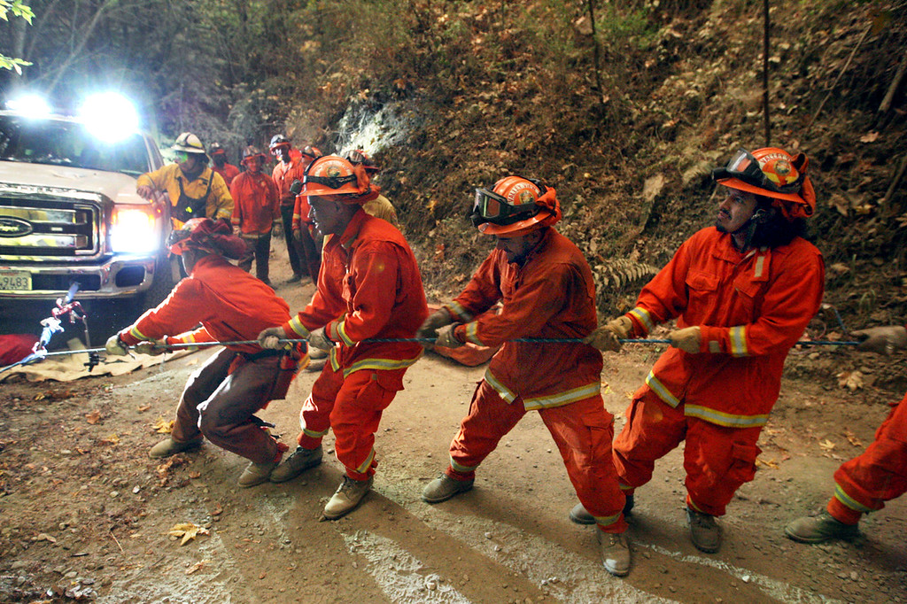 . California Department of Corrections and Rehabilitation imate crews man the rope in pulling firefighters up a near-vertical canyon wall after battling the Bear Fire off Bear Creek Road early Tuesday. (Dan  Coyro -- Santa Cruz Sentinel)