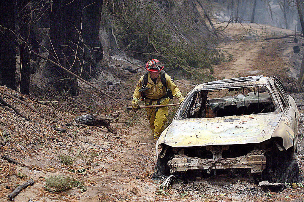 . A Cal Fire crew member makes his way past a burned out car off Bear Creek Canyon Road after the Bear Fire swept through early Tuesday morning. (Dan  Coyro -- Santa Cruz Sentinel)