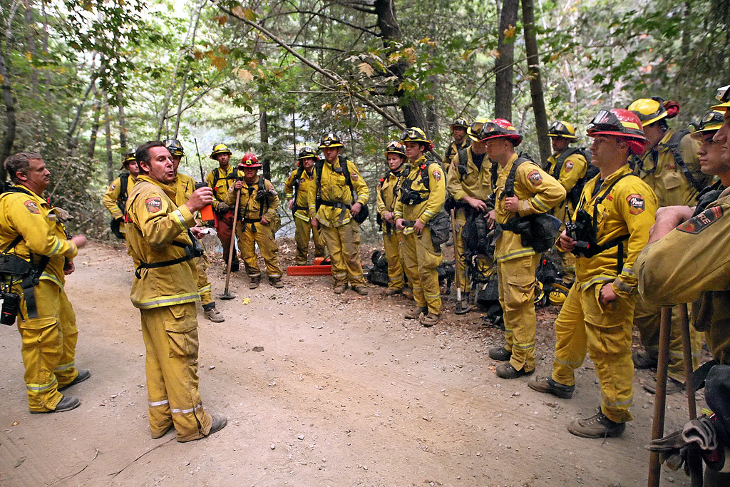 . Cal Fire Captain Sean Adams, second from left, speaks to his crew, evaluating their performance in fighting the Bear Fire off Bear Creek Road in the Santa Cruz Mountains early Tuesday morning. (Dan  Coyro -- Santa Cruz Sentinel)