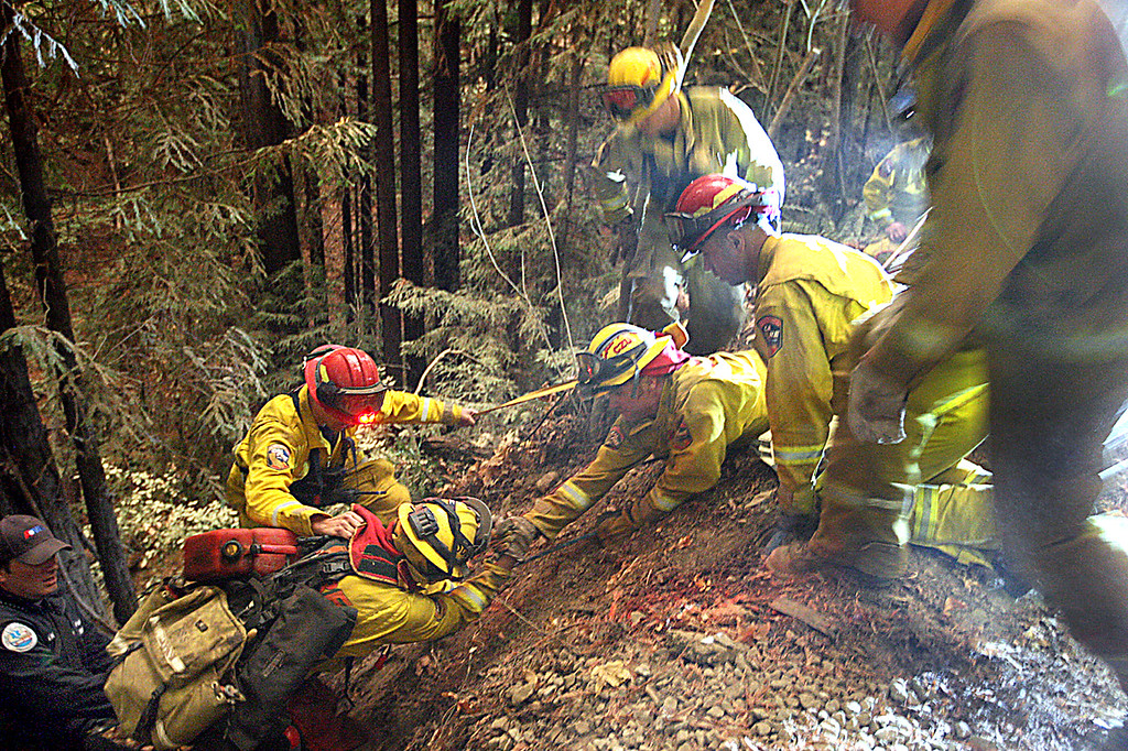 . Cal Fire crews use a rope to pull their firefighters up a near-vertical canyon wall after battling the Bear Fire in the early morning hours Tuesday. (Dan  Coyro -- Santa Cruz Sentinel)