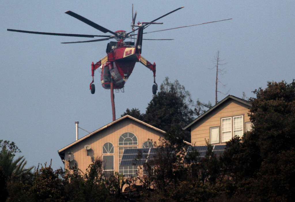 . A Cal Fire Sikorsky S-64 Skycrane helicopter passes over a house that rises above Bear Creek Canyon Road to make a water drop on the Bear Fire Wednesday. (Shmuel Thaler -- Santa Cruz Sentinel)