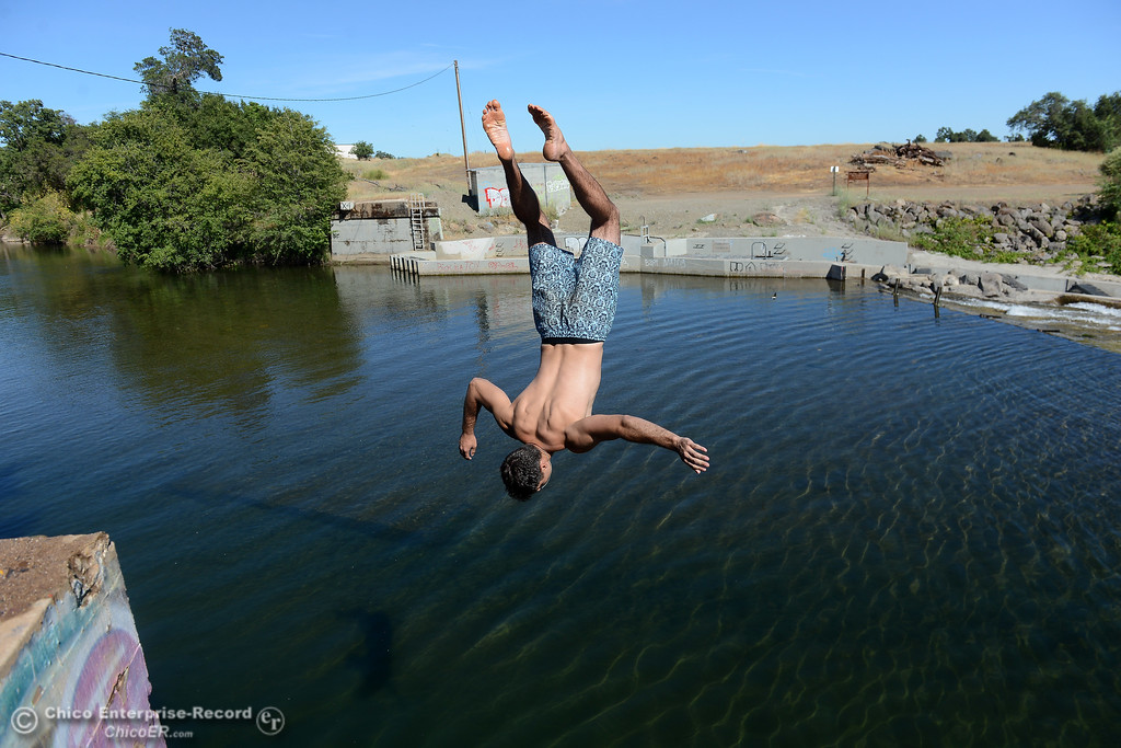 . Chico State student Brandon Michelucci does a backflip into Butte Creek as people beat the heat Friday, June 16, 2017, in the Butte Creek Ecological Preservein Chico, California. (Dan Reidel -- Enterprise-Record)