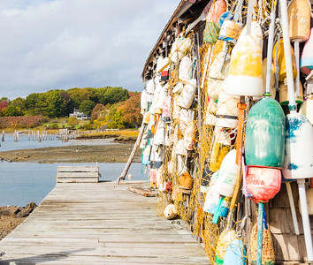 Colorful buoys hanging on an oar house