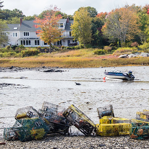 Lobster pots and boat at low tide
