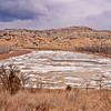 An oxbow on the Little Missouri River brings the spring's ice floe up next to the Long X road, a 30-mile road snaking through the Badlands between Watford City, and Killdeer, North Dakota.  Rain clouds to the north hasten the snow melt -- what little snow melt there is.  It's been a dry year for snow.