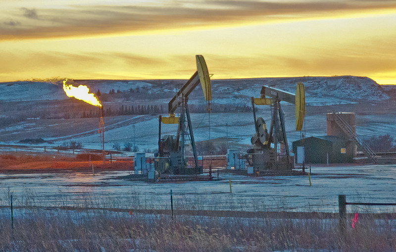 Sunset provides a golden backrop behind two oil pumps and the natural gas flare.  Some people are upset by the flaring, claiming it's an environmental hazard.  What they don't  acknowledge is that flaring today is about a third of what it has been historically and continues to drop as recovery methods are enhanced and improved to capture the natural gas.