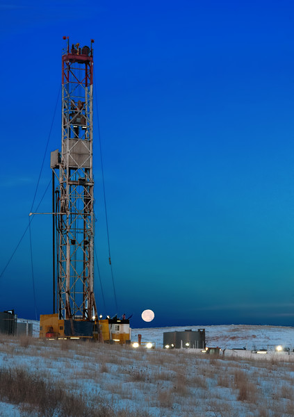 The December moon is barely gone as it sets in the west as the early morning moon rises in the east lighting up the non-stop work of the drilling rig west of Watford City