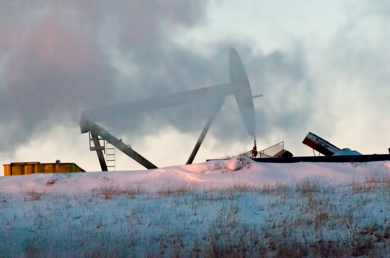 Fracking steam drifts from a nearby rig to surround the working pump on the well pad east of New Town, North Dakota.