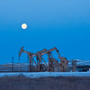 West of Watford City, early in the morning as the moon descends, just before the sun rises in the opposite sky, three pumps continue their endless motion to bring shale oil to the surface.