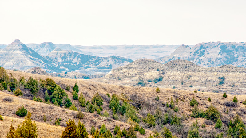 "In southern Billings County, ND, a hazy day softens the look of the Badlands.<br /> <br /> You can own this image as wall decor, mouse pad, coffee cup or other product.  Just click ""buy"" to browse the products you can buy here."