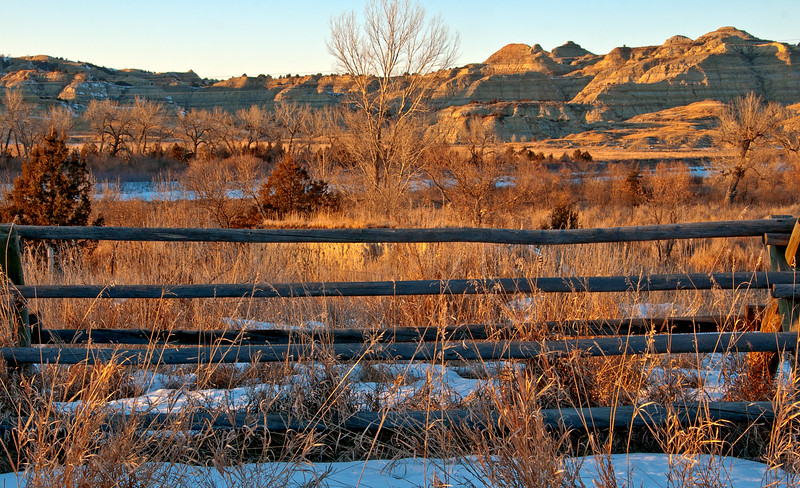 The slope of the Badlands that face south toward the winter sun stay relatively free of snow all winter.  From the Long X road to the CCC campground, south of Watford City, the horizontal rails in the fence are repeated in the layers of the bluffs on the other side of the Little Missouri River
