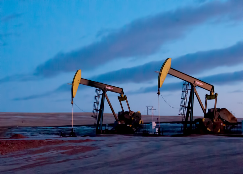 The evening sun illuminates two pumps in McKenzie County, North Dakota south of Watford City.  The golden hour, in the last moments of the day create a dark backdrop to illuminate the long slow strokes of the oil pumps.